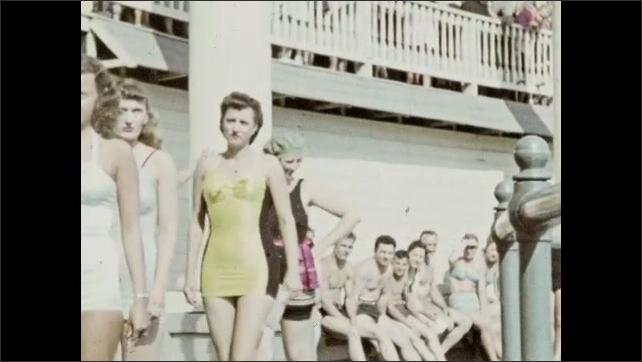 1940s: Women in bathing suits walk in a single file line.