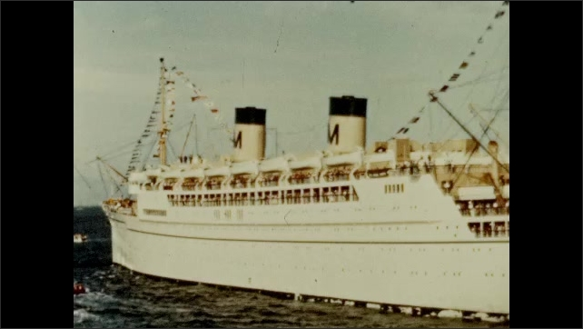 """1950s: Title card that says """"Arrival in Honolulu."""" Cruise ship in water with smaller boats nearby."""