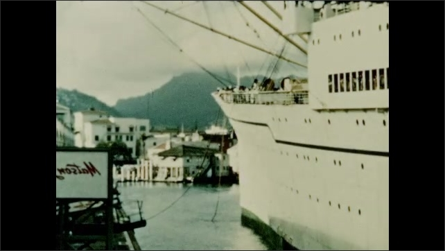 1950s: Passengers at railing of deck on cruise ship. Ship approaches shore.