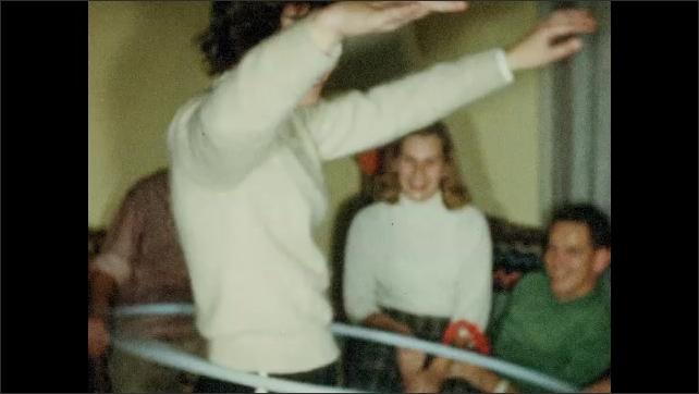 1950s: Woman jumps through hula hoop. Woman hula hoops.
