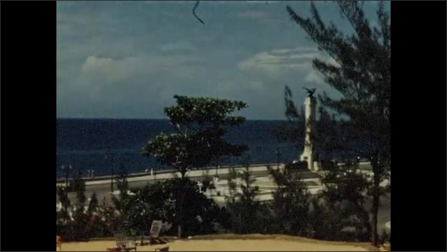 1940s: Palm trees sway off veranda of hotel building. Monument by side of freeway, next to shore.