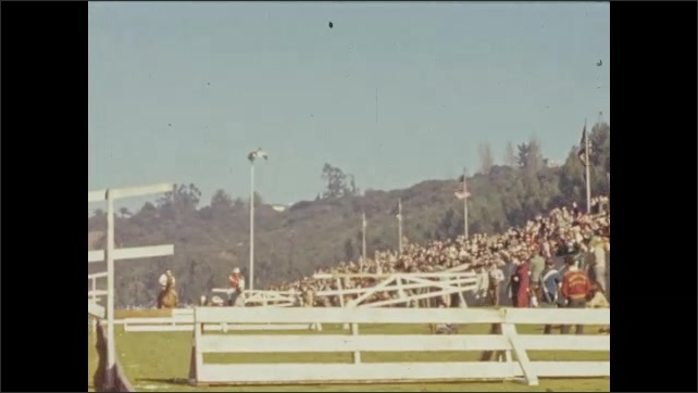 1940s: Man in suit is talking. Spectators sit on sidelines of horse show. Horses jump obstacles as crowd watches.