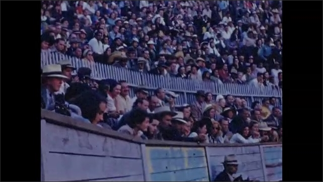 1940s: Crowd in stands at bullfighting arena. Man walks into ring, walks up to bull, taunts bull with cape, bull charges at man.