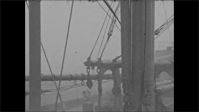 1940s: Waves splash over deck of ship. Waves splash against masts. Waves crash over deck on a rough sea.