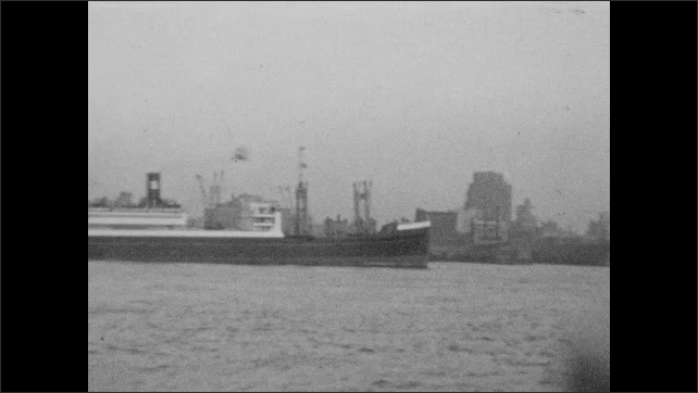 1940s: Cruise and cargo ships sit in bay near large city. Tugboats drive past large ships in bay.