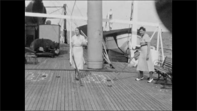 1940s: Waves heave in ocean. Women talk and play shuffleboard on deck of ship. Man shows woman how to play shuffleboard.