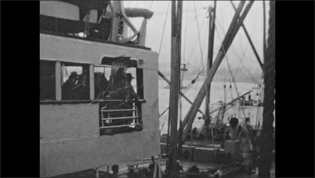 1940s: Passengers wave goodbye from deck. Streamers hang from deck of ship as passengers wave goodbye. Men and women wave goodbye from dock. Streamers hang from ship as passengers wave goodbye.