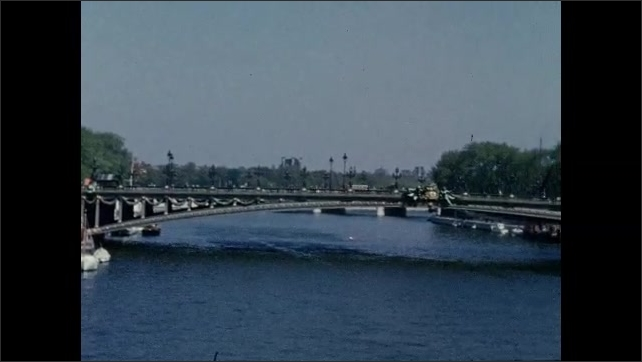 1940s: Boats near ornate bridge of the Seine river. Boats and barges float down river Seine.