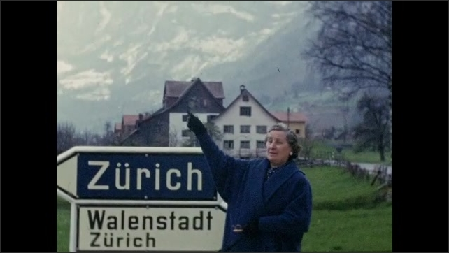 1940s: EUROPE: SWITZERLAND: man points at view. Lady and man by Raperswil Castle. Lady stands by Zurich sign. Lady points at mountains and snow.