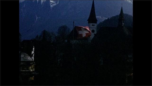 1940s: EUROPE: SWITZERLAND: View towards Jungfrau mountain. Buildings in Switzerland. Swiss flag blow in wind.