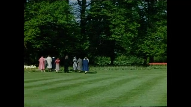 1940s: EUROPE: FRANCE: Grass lawn in palace gardens. Visitors walk across grass on tour. Lady looks at camera.