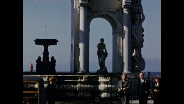 1940s: EUROPE: ITALY: Arch in city. Statues under arch. People visit monument in Italy. People wave at camera.