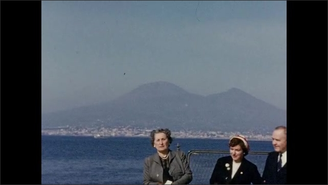 1940s: EUROPE: ITALY: View across sea in Naples. Lady looks at camera. Lady talks to camera.  Lady and man wave at camera