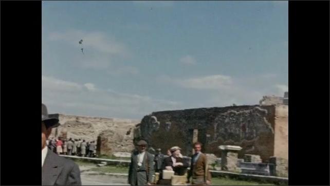 1940s: EUROPE: ITALY: Visitors walk along path through Pompeii. Ruins at Pompeii.