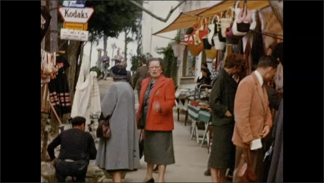 1940s: EUROPE: ITALY: Lady visits bazaar in street. Lady speaks to camera. Lady shopping for souvenirs