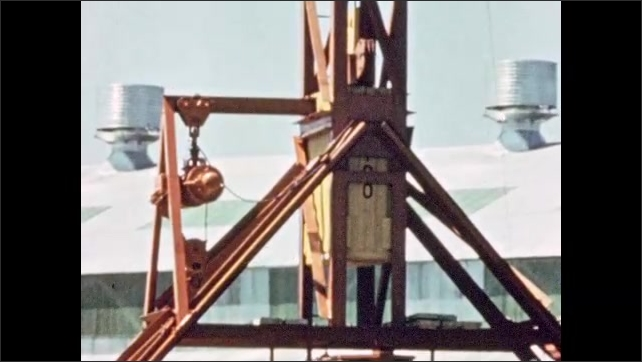 1950s: Men stand.  Weight is pulled up tower.  Weight is dropped on tank.  Tank jumps.