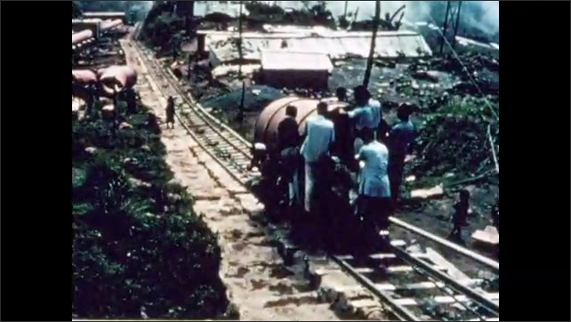 1950s: Cable lowers cart carrying large pipe down hill.  Tracks.  Men ride cart.  People watch.