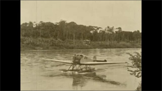 1930s: COLUMBIA: SOUTH AMERICA: hydroplane lands on San Juan River in Choco district. Man stands on wing of plane.