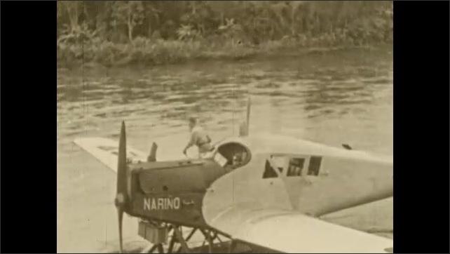 1930s: COLUMBIA: SOUTH AMERICA: hydroplane on San Juan River. Nariño hydroplane. Man stands on hydroplane.