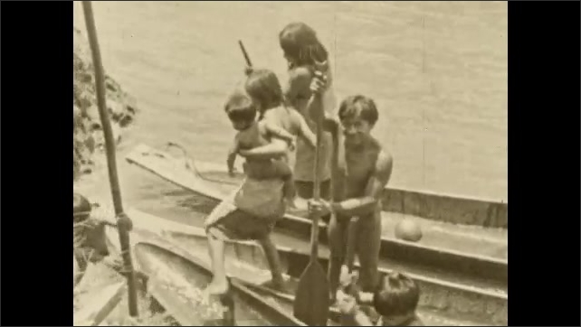 1930s: COLUMBIA: SOUTH AMERICA: tribe members in canoe. Lady carries baby from canoe.