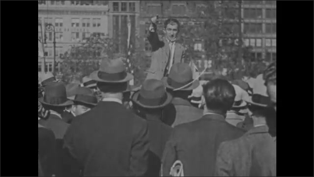 1930s: Man stands before crowd, giving speech.