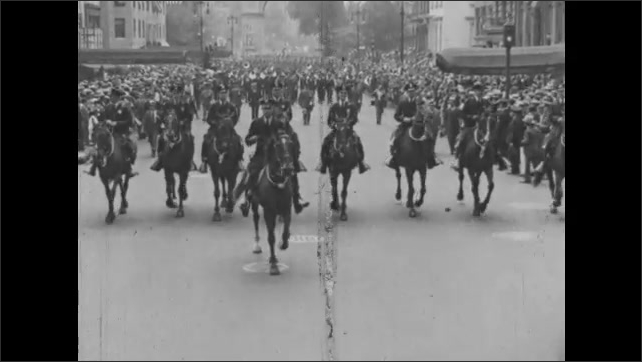 1930s: Police officers on horse back lead procession down street for parade.