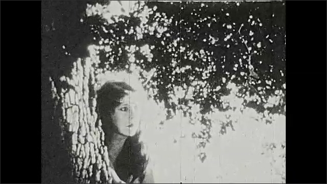 1920s: Woman walks through woods. Snake slithers on tree branch. Woman leans around tree and stretches arm out. Snake slithers past tree trunk.