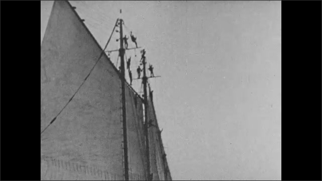 1930s: UNITED STATES: sailing boat on water. Men wave from sails of tall ship. Waves at bow of sailing ship.