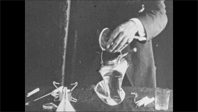 1930s: UNITED STATES: weight of air experiment with can. Affect of air pressure on can. Collapsed metal container. Man picks up damaged can.
