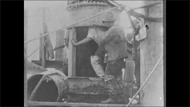 1930s: UNITED STATES: men go down into caisson to dog down to bed rock. Caisson on river bed. Men climb into chamber. Man closes chamber door.