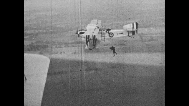 1930s: UNITED STATES: plane flies in sky. Slow motion of man parachuting from early plane. Air flows over wing of plane.