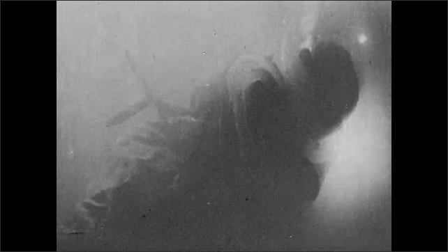 1930s: UNITED STATES: diver under water in suit. Diver uses electric torch under water.