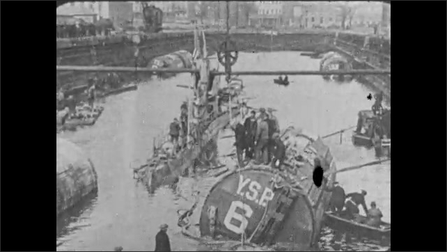 1930s: UNITED STATES: sunken ship raised to surface by pontoons filled with air. Men on submarine. Men on boat make repairs to submarine