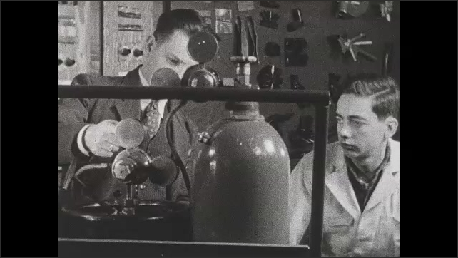 1940s: Hand takes a working pressure key. Hand screws the key into the acetylene regulator. Man points to the acetylene regulator and talks to young man. Intertitle.