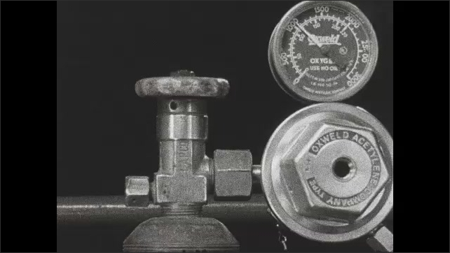 1940s: Hand opens oxygen tank valve, pencil points to regulator which goes up. Intertitle. Hand takes a working pressure key. Hand screws key into regulator, pencil points to regulator which goes up.
