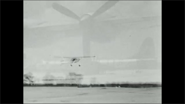 1950s: Private prop-plane goes down runway and takes off. Military bombers and planes on tarmac.