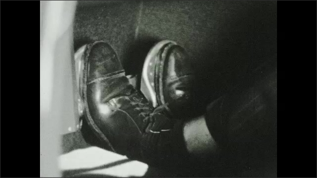 1950s: Person in cockpit of plane adjusts knobs on dashboard, moves steering wheel and steps on pedals. Rudder on plane moves. Person pulls on steering wheel of plane.