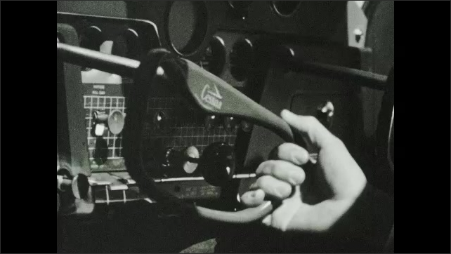 1950s: Elevators on tail of Cessna plane move up and down. Person in cockpit of plane turns steering wheel back and forth. Ailerons on wings move up and down. Plane flies in sky.