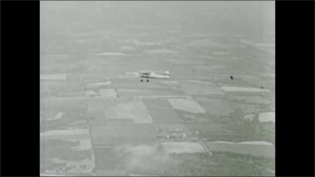 1950s: Rudder of Cessna plane moves to the right. Pilot in cockpit of plane turns steering wheel to right. Ailerons on wings move. Plane flies to right in sky.