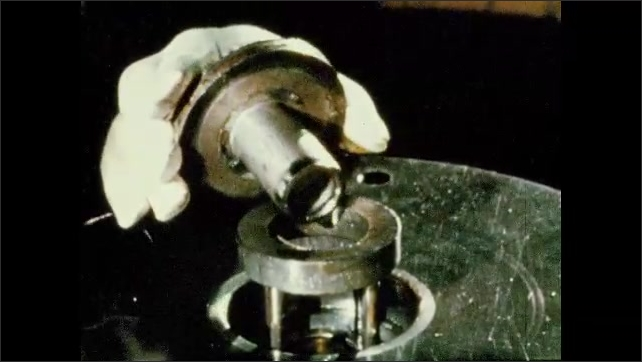 1950s: UNITED STATES: machine presses metal into shapes. Man works with machine in factory Metal press. Hand removes metal component. Water cools metal