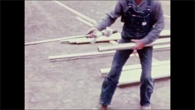 1950s: UNITED STATES: man moves pipes on rollers. Men join metal pipes together