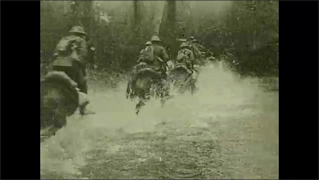1910s: Soldiers ride horses through shallow water. Team of horses pulls a cart.