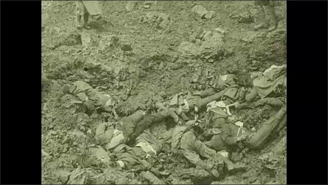 1910s: Explosions on hillside. Dead soldiers in a pile. Dead soldiers in the trenches.