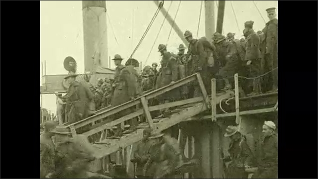 1910s: Soldiers disembark from ship. Soldier stands with a dog on the top of his pack, smiles, talks.