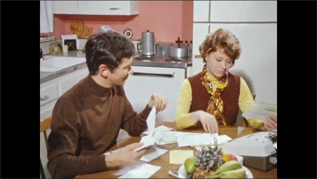 1970s: UNITED STATES: man and lady sit at breakfast table together. Lady puts pencil behind ears. Couple look through bills.