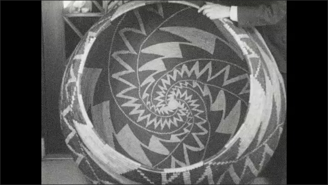 1930s: Woven basket large enough to hold a person is held up and shown.