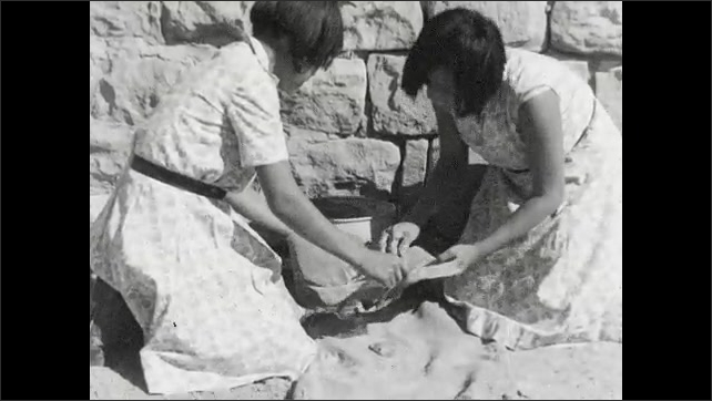 """1930s: Intertitle """"After breaking the rough clay, and mixing it with water, the artist rolls it into a coil and begins to build up the vessel"""". Women build and smooth clay."""