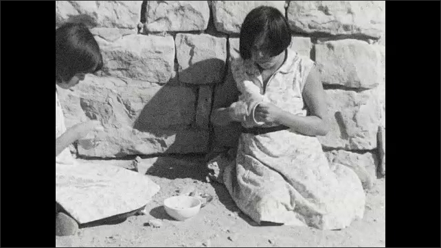 1930s: Women sit outside building and forming clay bowls.
