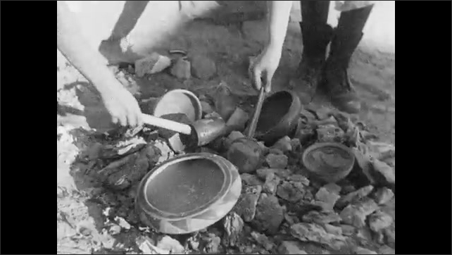 1930s: Women use sticks to push ashes away and remove baked pottery from fire.