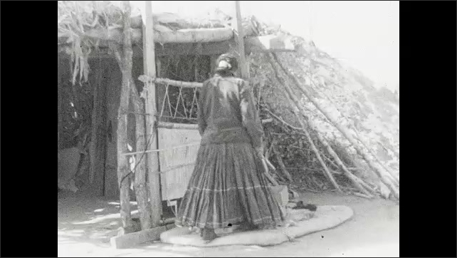 """1930s: Intertitle """"The making of Navajo blankets is another living art of the Southwest. The wool is grown by the Navajos themselves"""". Woman walks outside and kneels on the ground."""
